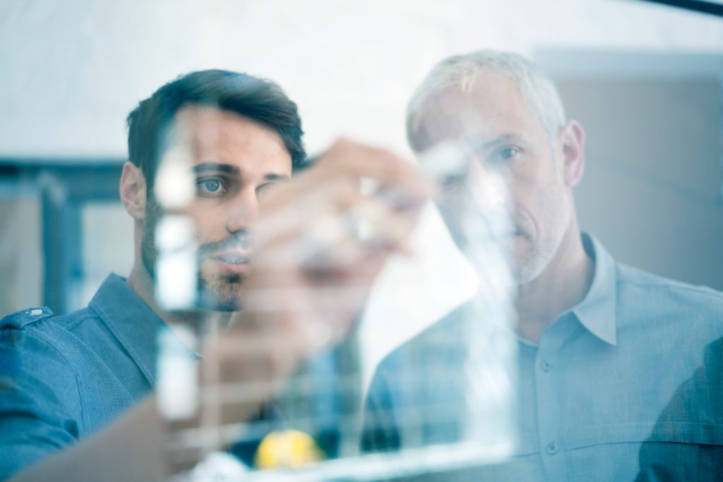 A photo of businessmen making plan on glass wall. Concentrated executive is explaining strategy to colleague. Professionals are at workplace.